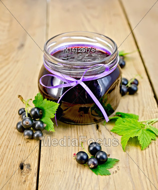 Black Currant Jam In A Glass Jar, Fresh Black Currant Berries With Leaves On A Wooden Board Stock Photo