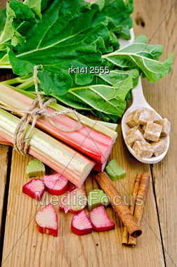 Bundle Of Stalks Rhubarb, Cut Pieces Of Rhubarb With A Sheet Of Sugar Cubes In A Spoon, Cinnamon On A Wooden Board Stock Photo