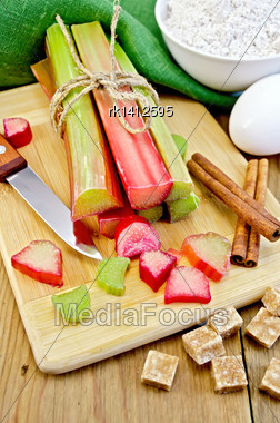 Bundle Of Stalks Rhubarb, Cut Pieces Of Rhubarb, Knife, Sugar Cubes, Cinnamon, Eggs, Flour, Cloth On A Wooden Board Stock Photo