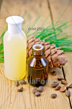 Cedar Oil And Lotion Bottles, Cedar Cone, Cedar Nuts On The Background Of Wooden Boards Stock Photo