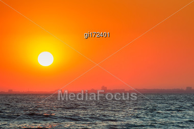 City On The Coast In The Light Of Sunset. Urban Buildings In The Backlight Stock Photo