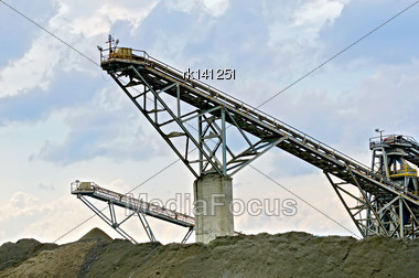 Equipment For The Production Of Crushed Stone On A Background Of Blue Sky And Clouds Stock Photo