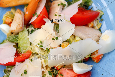 Fresh Salad Of Chicken With Vegetables And Cheese, On A Blue Background Stock Photo
