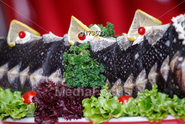 Fried Sturgeon, Decorated With Lemons And Greens Stock Photo