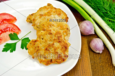 Fritters With Chicken Meat On A White Plate With Tomato And Parsley, Dill, Onion, Garlic On A Wooden Board Stock Photo