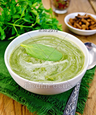 Green Soup Puree In White Bowl With Spoon, Napkin, Parsley, Croutons, Peppers On A Wooden Boards Background Stock Photo
