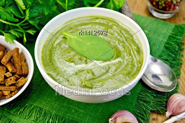 Green Soup Puree In White Bowl With Spoon, Napkin, Parsley, Croutons, Pepper, Garlic On A Wooden Boards Background Stock Photo
