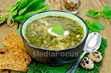 Green Soup Of Sorrel, Nettle And Spinach In A Bowl, Spoon, Bread, Pepper, Quail Eggs On A Wooden Board Stock Photo