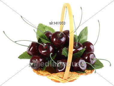 Heap Of Artificial Several Cherries With Leafs In Yellow Basket. Isolated On White Background. Close-up. Studio Photography Stock Photo