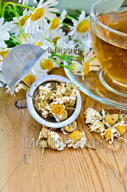 Herbal Tea In A Glass Cup, Metal Sieve With Dry Chamomile Flowers, Fresh Flowers, Daisies, Doily On A Wooden Board Stock Photo
