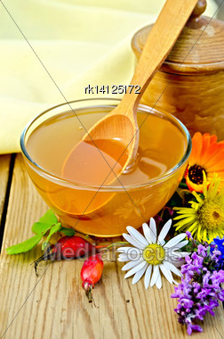 Honey In A Glass Bowl And A Wooden Pot, Spoon, Rosehip Berries, Flowers, Napkin On The Background Of Wooden Boards Stock Photo