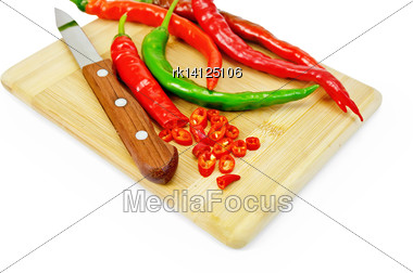 Hot Pepper Red And Green With A Knife On A Wooden Board Isolated On White Background Stock Photo