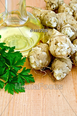 Jerusalem Artichoke Tubers With Parsley And Carafe With Vegetable Oil On A Wooden Board Stock Photo