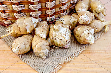 Jerusalem Artichoke Tubers, Wicker Basket On Burlap Background Napkin Of Burlap And Wooden Boards Stock Photo