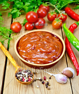 Ketchup In Pottery, Tomatoes, Parsley, Hot Pepper, Garlic, A Spoon With Peppercorns, On A Background Of Wooden Boards Stock Photo