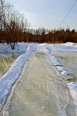 Melting Ice On The River, Melted Road Alternating River, Snow, Bushes And Trees On The Shore Against The Blue Sky Stock Photo