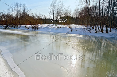 Melting Ice On The River, Snow, Bushes And Trees On The Shore Against The Blue Sky Stock Photo