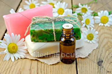 Oil In A Bottle, Different Soaps On A Piece Of Paper, Daisy Flowers On A Background Of Wooden Boards Stock Photo