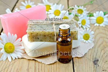 Oil In A Bottle, Homemade Soap On A Piece Of Paper, Daisy Flowers On A Background Of Wooden Boards Stock Photo