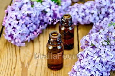 Oil In A Bottle, Lilac Flowers On The Background Of Wooden Boards Stock Photo