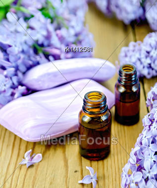 Oil In A Bottle, Soap, Lilac Flowers On The Background Of Wooden Boards Stock Photo