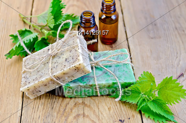 Oil In Bottles, Two Bars Of Homemade Soap With Twine, Nettle On The Background Of Wooden Boards Stock Photo