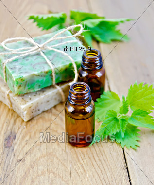 Oil In Bottles, Two Bars Of Homemade Soap, Nettle On The Background Of Wooden Boards Stock Photo