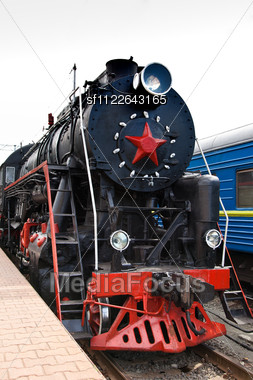 Old Steam Train Is Leaving A Station. Vintage Steam Engine Locomotive Train Moving Down Railroad Track Towards Camera. Stock Photo