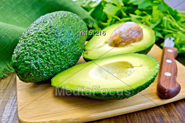 One Whole And One Cut In Half Avocado, Knife, Parsley, Green Cloth On A Wooden Boards Background Stock Photo