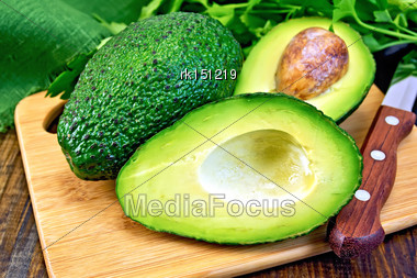 One Whole And One Cut In Half Avocado, Knife, Parsley, Napkin On A Wooden Boards Background Stock Photo