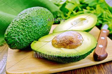 One Whole And One Halved Avocado With Bone, Knife, Parsley, Green Cloth On A Wooden Boards Background Stock Photo