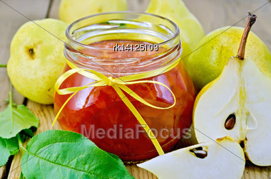 Pear Jam In A Glass Jar, Fresh Pears, Twigs With Leaves On The Background Of Wooden Boards Stock Photo