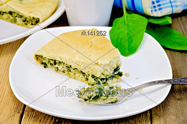 Pie With Spinach And Cheese On A Plate, Spinach Leaves, Mug, Fork, Napkin On Wooden Board Stock Photo