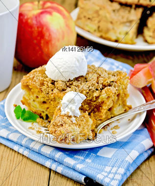 Piece Of Sweet Cake With Rhubarb, Apples And A Scoop Of Ice Cream, Mint, Napkin, Fork, Cup On The Background Of Wooden Boards Stock Photo