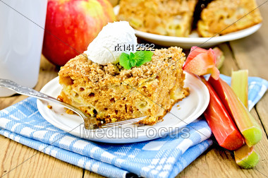 Piece Of Sweet Cake With Rhubarb, Apples And A Scoop Of Ice Cream, Mint, Napkin, Cup On The Background Of Wooden Boards Stock Photo