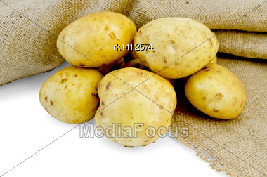 Pile Of Yellow Potato Tuber With A Cloth Sack Isolated On White Background Stock Photo