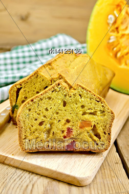 Pumpkin Cake With Candied Fruit On The Board, Pumpkin, Knife, Napkin On The Background Of Wooden Boards Stock Photo