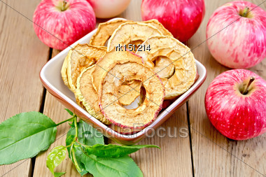 Red Apples Fresh And Dried In An Earthenware Bowl, Green Leaves On A Wooden Boards Background Stock Photo