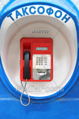 Red Payphone In Blue Booth On Outdoor Wall. Close-up Stock Photo