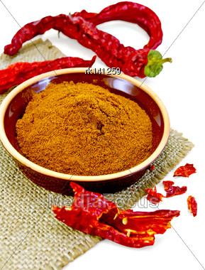 Red Pepper Powder In A Clay Bowl, Red Pepper Pods On A Napkin From A Sacking Isolated On White Background Stock Photo