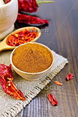 Red Pepper Powder In A Wooden Bowl, Cereal And Dry Chili Pepper Pods In A Wooden Spoon And A Mortar, Sacking On A Wooden Board Stock Photo