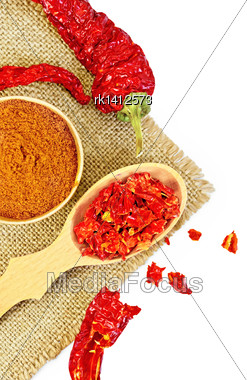 Red Pepper Powder In A Wooden Bowl, Cereal And Pods Of Red Pepper On A Napkin From A Sacking Isolated On White Background Stock Photo
