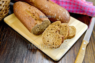 Rye Baguettes On A Board With A Knife, A Wicker Basket, Napkin On A Dark Wooden Board Stock Photo
