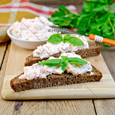 Sandwiches On Two Pieces Of Rye Bread With Cream Of Salmon And Mayonnaise, Basil, Napkin, Parsley On A Wooden Boards Background Stock Photo