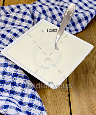 Sour Cream In A White Square Bowl, Blue Checkered Napkin, Spoon On A Wooden Boards Background Stock Photo