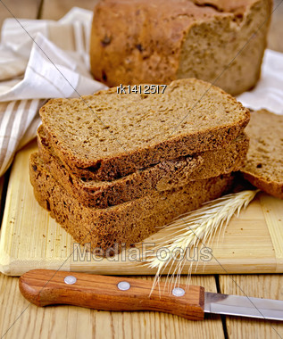 Stack Of Slices Of Rye Homemade Bread With A Knife And Rye Spikelet On Plate, Napkin, Loaf Of Bread On A Wooden Board Stock Photo