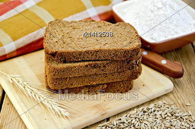 Stack Of Slices Of Rye Homemade Bread With A Knife And Rye Spikelet On Plate, Napkin, Knife, Flour And Grains On A Wooden Board Stock Photo