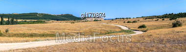 Steppe Road Stretches Into The Distance To The Rocks On The Background Of Blue Sky Stock Photo