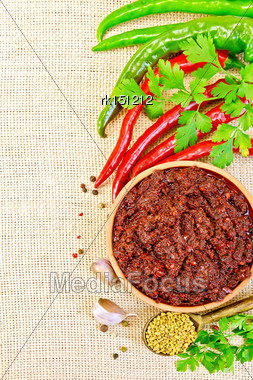 Tabasco Adjika In A Clay Cup, Hot Pepper, Garlic, Parsley, Fenugreek On The Background Of Sack Cloth Stock Photo