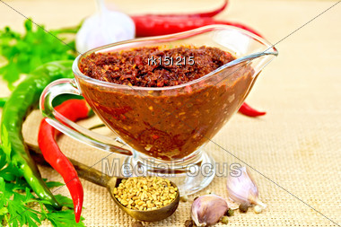 Tabasco Adjika In A Glass Gravy Boat, Hot Pepper, Garlic, Parsley, Fenugreek On The Background Of Sack Cloth Stock Photo